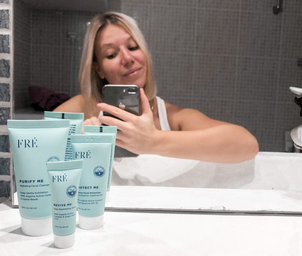 Skincare products in front of a mirror and woman reflecting from the mirror